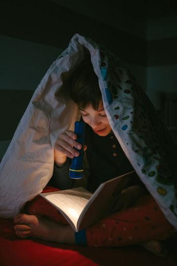 Boy reading book with flashlight in darkroom