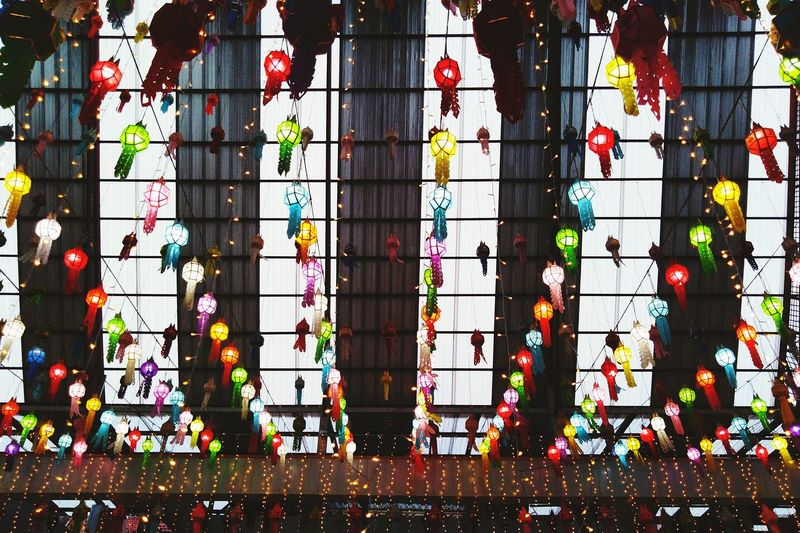 Low angle view of multi colored lights hanging in building