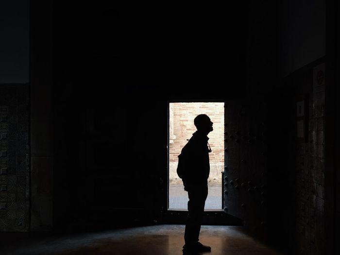 Silhouette man walking in building