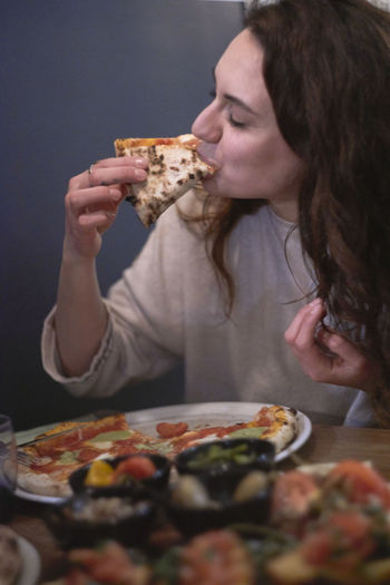 Close-up of woman eating pizza at table