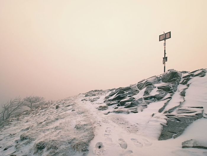 Rocky hill above inverse mist. winter cold weather in mountains colorful fog. misty prak in winter