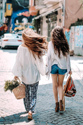 Two hippie women friends walking on a sunny day with a backpack, a basket of flowers. freedom concep