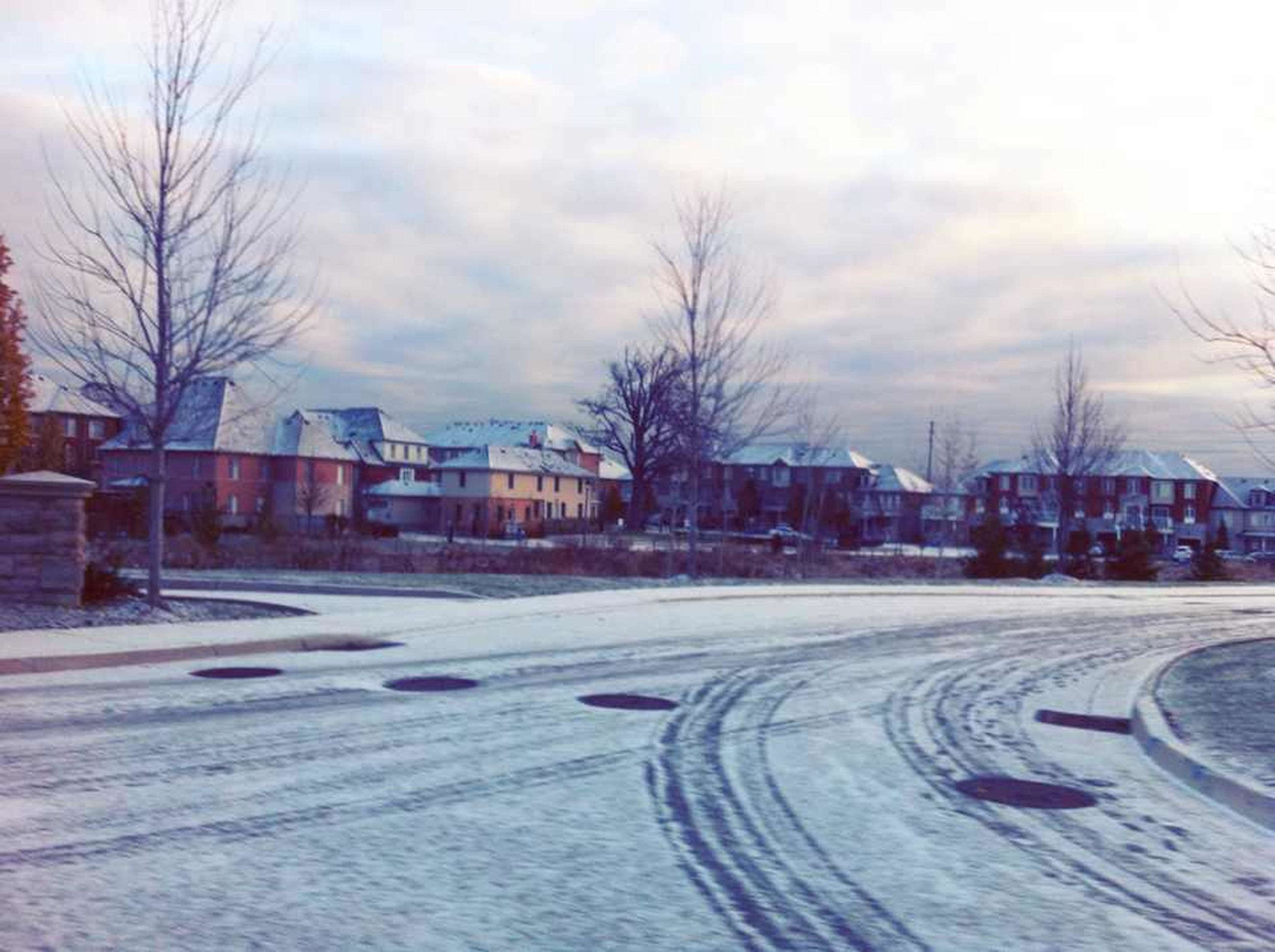 snow, cold temperature, winter, bare tree, weather, building exterior, season, transportation, road, street, sky, tree, architecture, built structure, city, car, cloud - sky, covering, the way forward, land vehicle