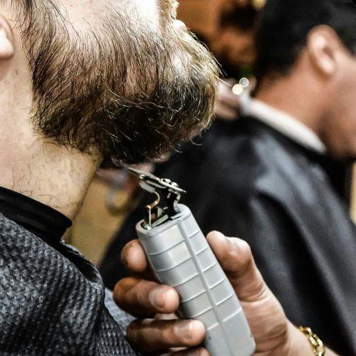 Cropped hand shaving man beard with electric razor
