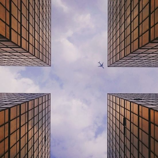 Low angle view of four modern buildings against cloudy sky