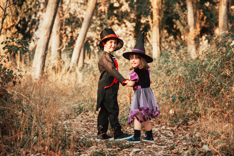 Full length portrait of girl wearing witch hat standing with brother at forest during halloween
