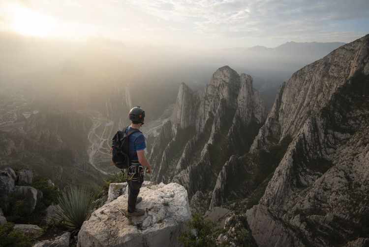 Full length of man looking at mountains against sky