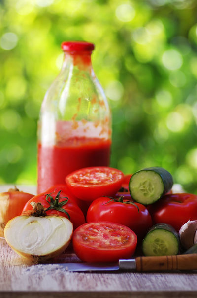 ripe tomatoes and glass bottle of tomato paste Bottle Close-up Container Cucumber Food Food And Drink Freshness Fruit Healthy Eating Pepper Red Ripe Tomatoes Table Tomato Tomato Paste Vegetable