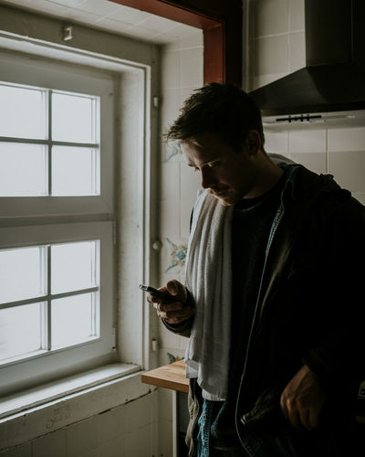 One Person Standing Indoors  Lifestyles Young Adult Holding Smartphone Man Kitchen Apartment