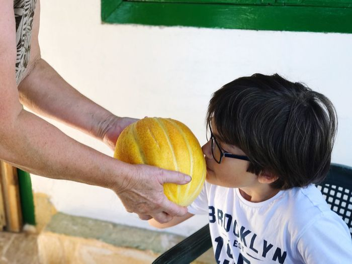 Cropped hands with melon holding by child