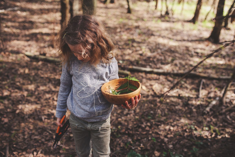 Girl Holding Bowl With Leaves And Pliers While Standing On Field In Forest
