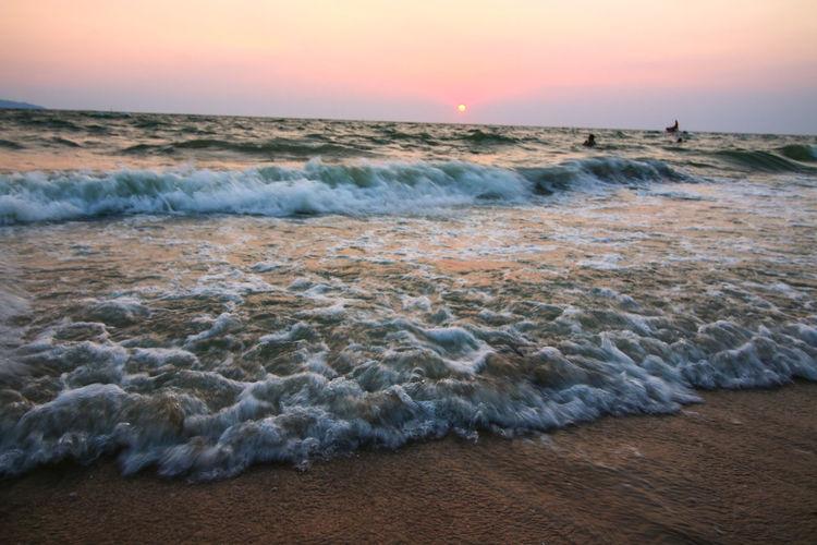 Waves rushing towards shore during sunset
