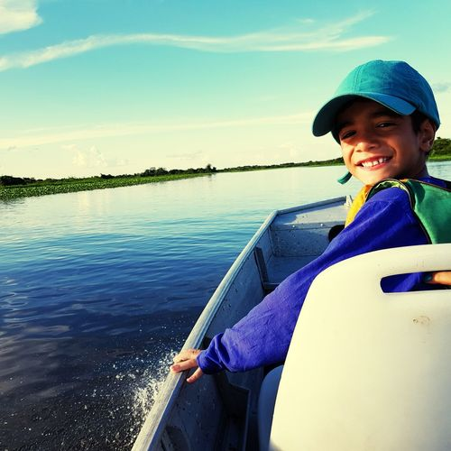 Portrait of smiling boy sitting in boat on lake against sky