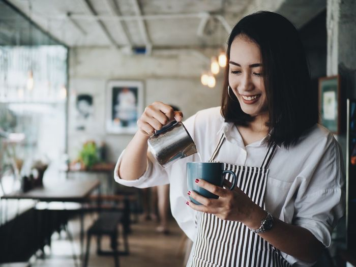 Young Woman Making Coffee On Counter At Cafe