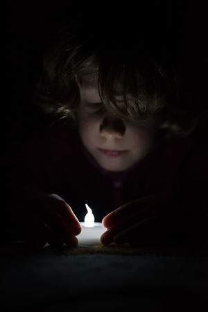 little girl fascinated by an artifical light Black Background Childhood Children Only Close-up Concentration Flame Headshot Illuminated Indoors  One Person People Real People