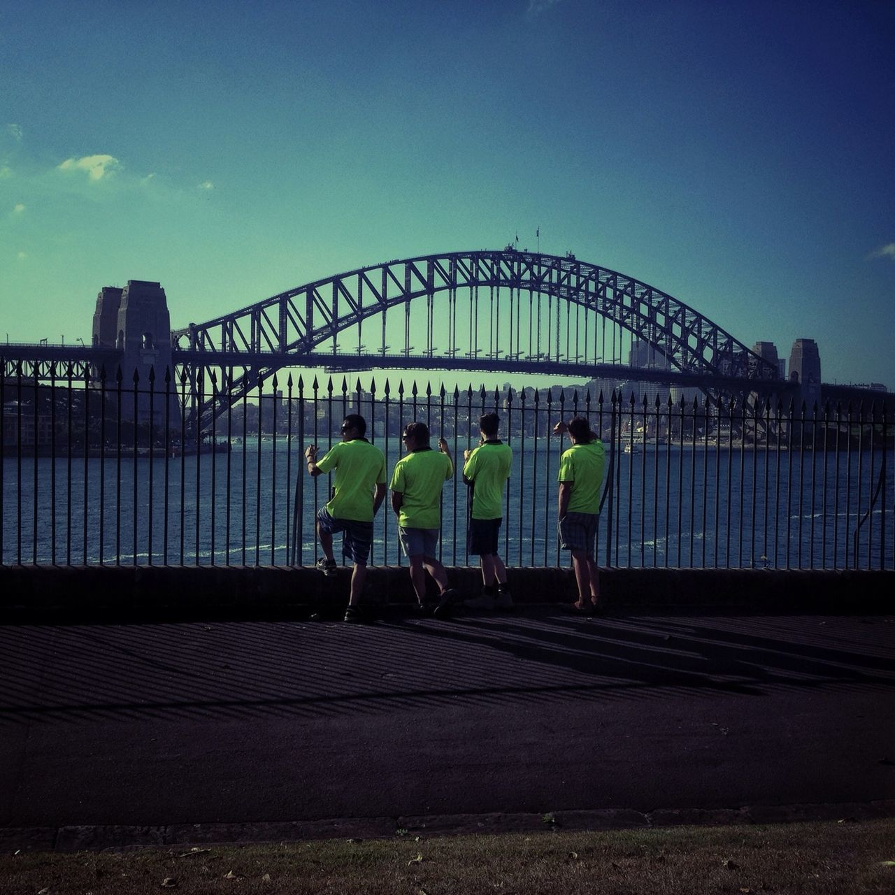 Rear view of four men standing against bridge over sea
