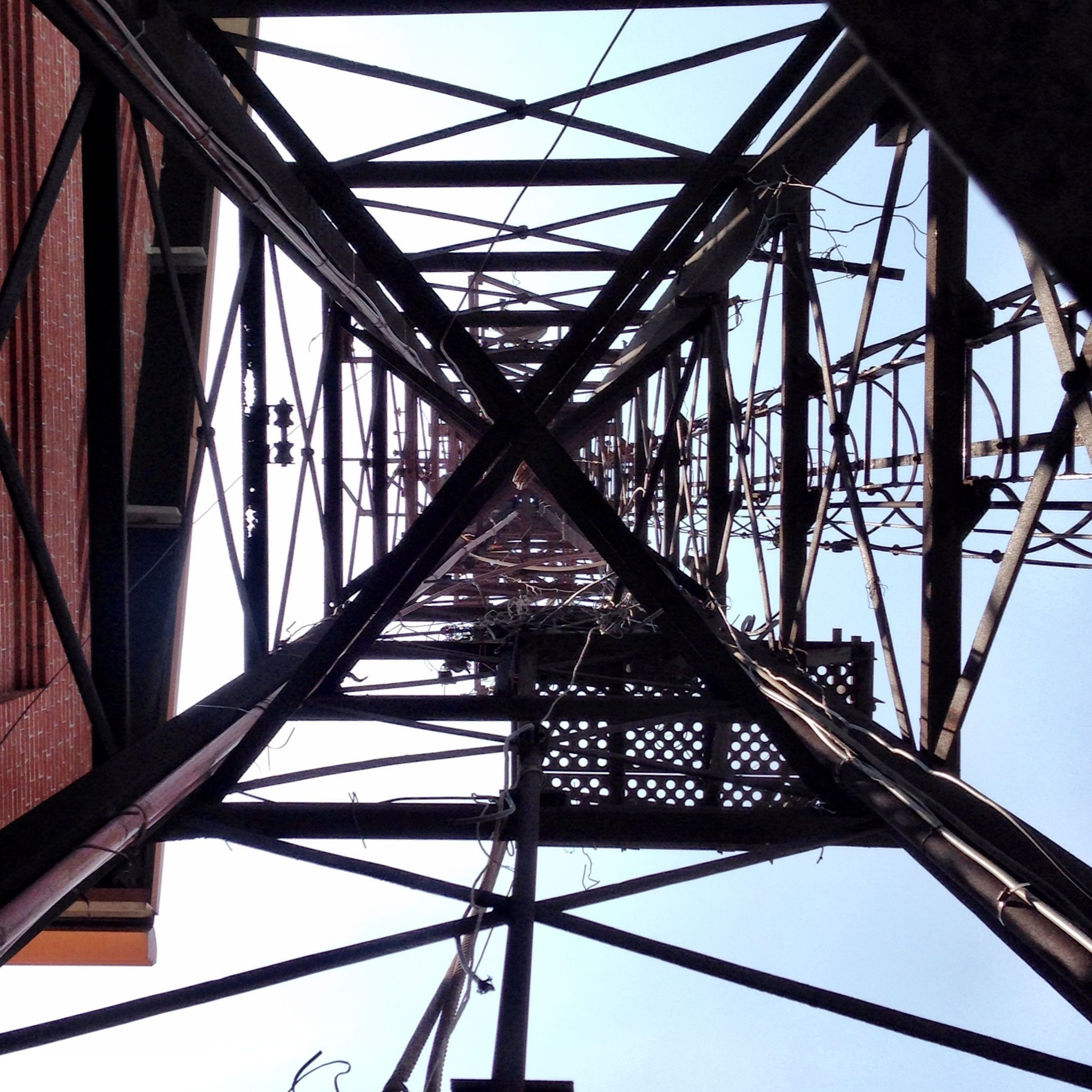 low angle view, connection, built structure, clear sky, electricity pylon, metal, architecture, sky, power line, power supply, directly below, metallic, day, cable, no people, grid, outdoors, electricity, part of, engineering