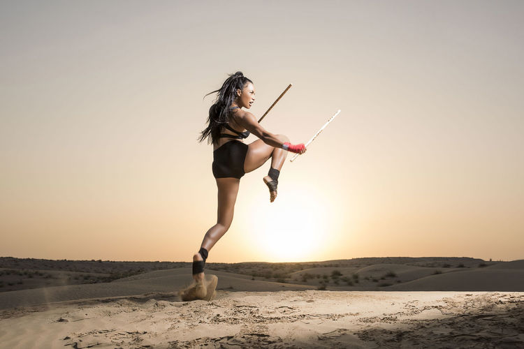 A Beautiful Asian-Black, Mixed Race martial artist female performs kicks, punches and stick fighting with creative leaps in the desert at sunrise or sunset wearing black short tights and black sports bra Desert Exotic Abs Asian Girl Blackandwhite Full Length Jumping Jumps Kickboxing Kicks Landscape Martial Artist Mixed Race Person One Person Sand Sand Dune Sports Wear Stick Fighting Sunrise Sunset Young Adult