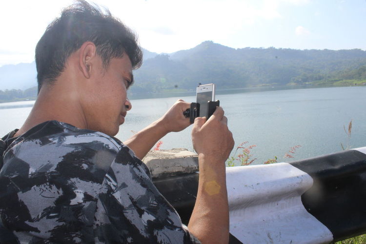 Young man using mobile phone against mountains