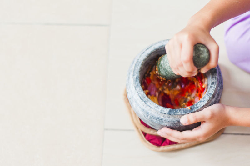 Cropped hands of woman mixing vegetable in mortar and pestle