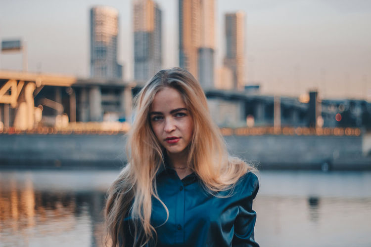 Portrait of beautiful woman against river in city