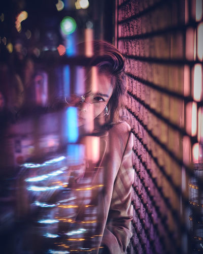 Portrait of young woman in nightclub seen through glass