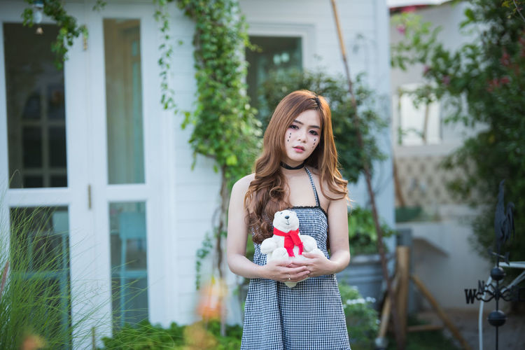 Portrait of young woman with face paint holding teddy bear while standing in yard
