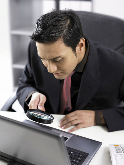 businessman holding a magnifying glass on keyboard Enlarge Looking At Camera Black Hair Businessman Communication Connection Curious Day Doublt Front View Holding Indoors  Laptop Looking Down Looking For Answers Magnified Magnifying Glass One Person Real People Search Sitting Technology Using Laptop Well-dressed Wireless Technology