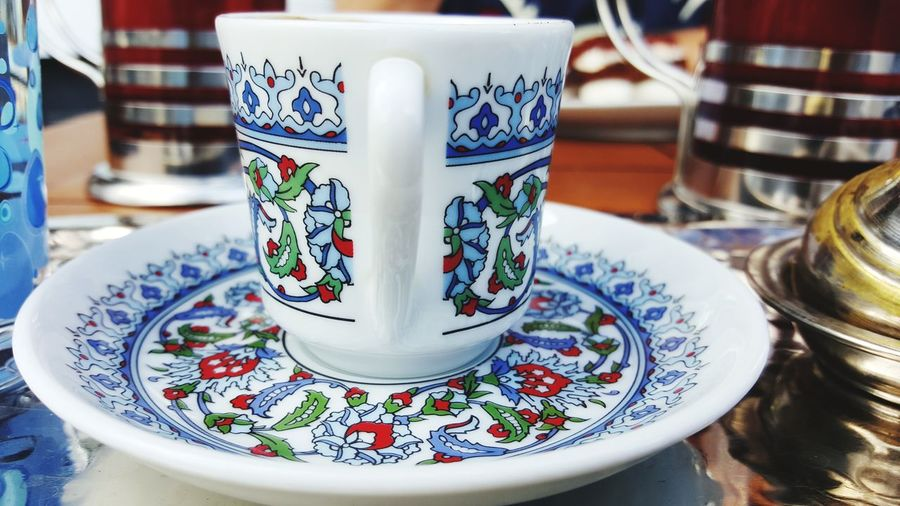 Close-Up Of Designed Tea Cup And Saucer On Table