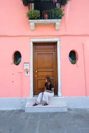woman sitting on door step in front of front door on pink background Architecture Building Exterior Built Structure Building Day Outdoors Venice Italy Burano Murano City Summer Pink Color Pink One Person Entrance Door Real People Lifestyles Women Adult Leisure Activity Young Adult Full Length Sitting Relaxation Young Women Front View Woman Girl Looking Away