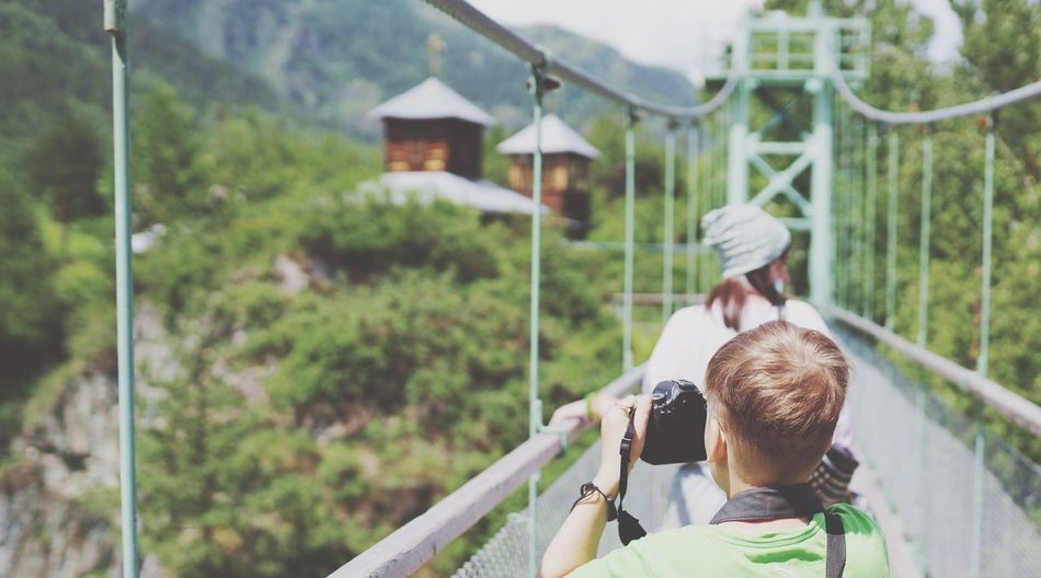 Rear view of boy photographing while standing on footbridge