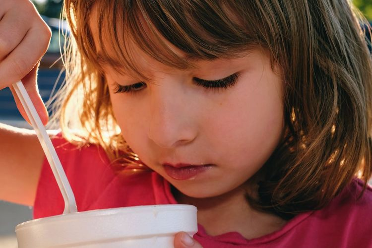 Close-up of girl eating food in container