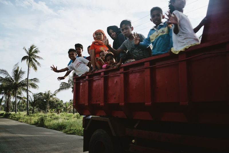 ASIA Children Daily Life Day Driving Driving By Happy INDONESIA Kids Maluku  Moluccas Morotaiisland On The Road Palm Trees People Red Truck Snapshot Sunny Day Transportation Travel Truck Vehicle Waving The Photojournalist - 2017 EyeEm Awards The Street Photographer - 2017 EyeEm Awards 10