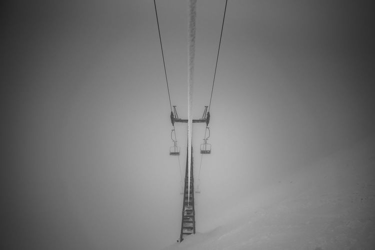 Electricity pylon against sky during winter