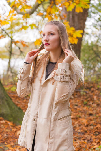 Young woman touching her blond hair while standing by trees during autumn
