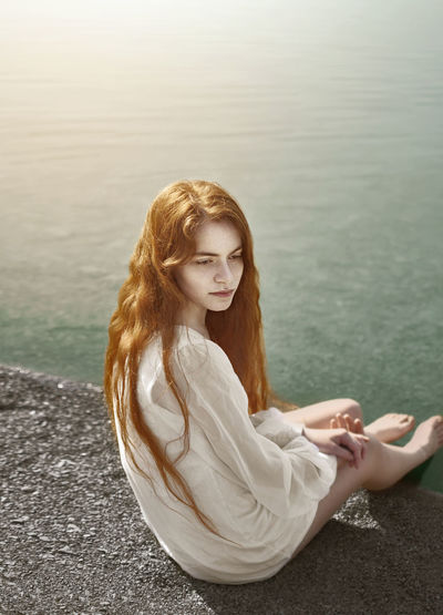 Feu Bank Of The River Pure Seashore Beautiful Woman Day Full Length Lake Lakeshore Leisure Activity Long Hair Marmaid Nature One Person Outdoors Purity Real People Redhead Relaxation Sea Seascape Sitting Water Women Young Adult Young Women