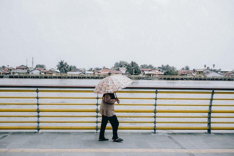 Full length of woman standing on railing during rainy season