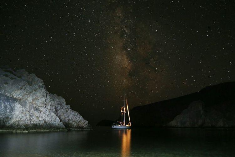 Illuminated sailboat sailing on sea against star field