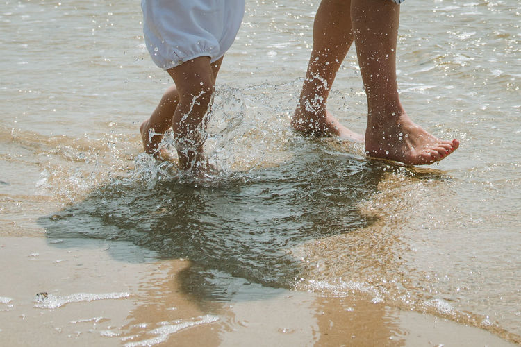 Low section of people splashing water at beach