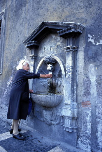 Adult Adults Only Black Dress Building Exterior Day Fetching Water Fountain Full Length Old Lady Old Woman One Person Outdoors People Public Fountain Real People Wall Water White Hair White Haired Old Lady White Haired Woman Woman