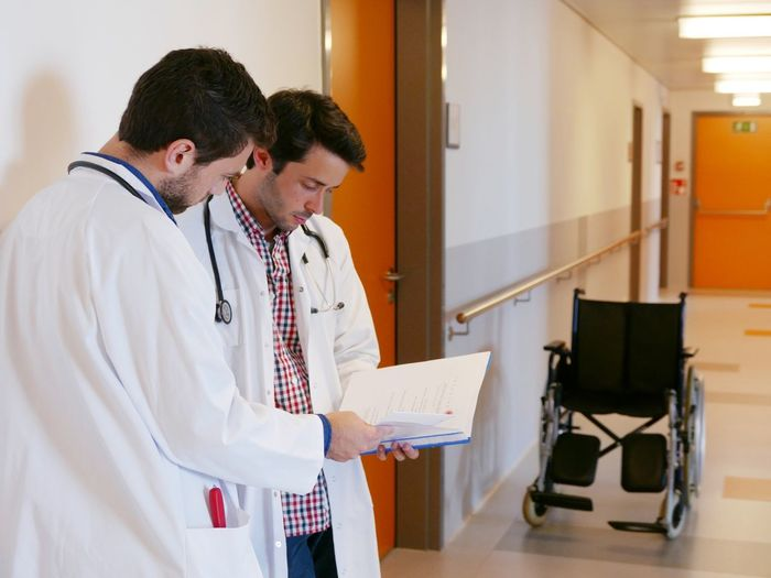 Male Doctors Discussing Over Document While Standing At Corridor In Hospital
