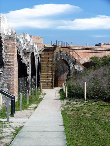 View of an area within Fort Barrancas Architectural Column Architecture Built Structure Cloud Cloud - Sky Day Diminishing Perspective Empty Footpath Fort Pickens Grass History Leading Narrow No People Outdoors Pathway Plant Sky The Past The Way Forward Travel Destinations Vanishing Point Walkway