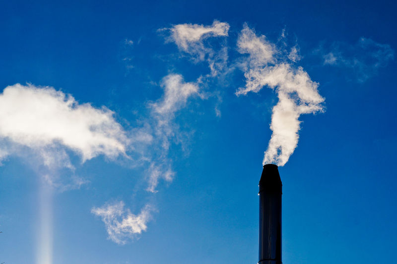 Silhouette of smoke stack against sky