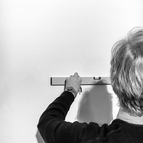 Cropped Image Of Man Marking On Wall With Level Ruler