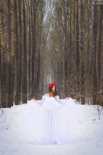Female Model Posing In White Dress Amidst Bare Trees During Winter