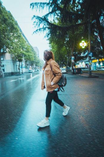 Woman walking on street in rain