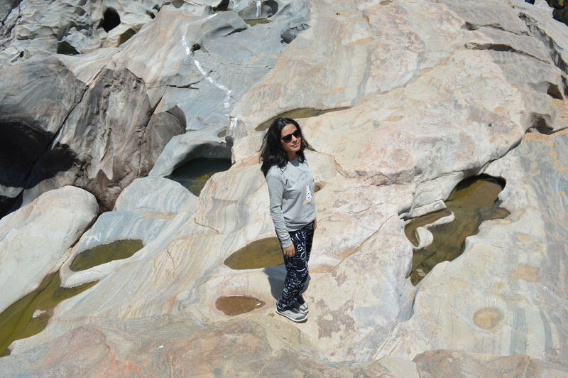 High angle view portrait of woman standing on rock