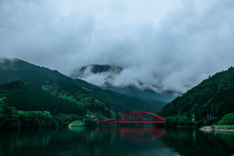 Bridge over lake against cloudy sky