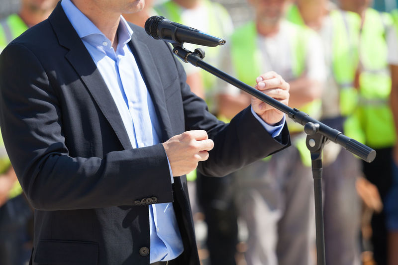 Midsection of businessman giving speech during press conference