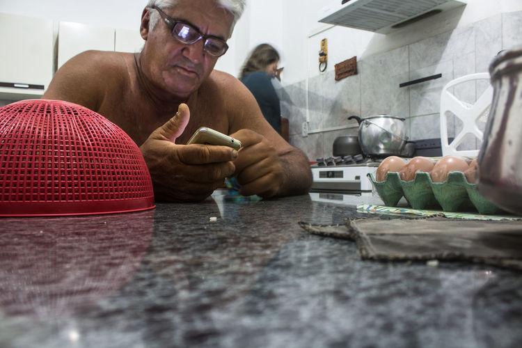Shirtless man using phone while sitting at kitchen island